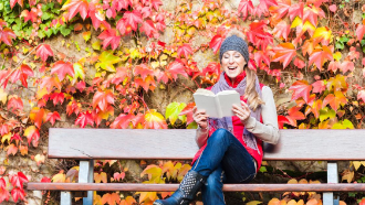 Woman sitting on a bench smiling and reading with fall foliage behind her