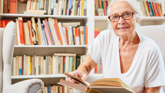 Senior Citizen Woman siting in front of a book case holding a book open and smiling