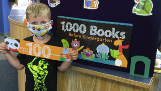 Little boy standing holding up a sign that says 1,000 Books