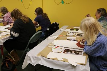 Adults painting at tables