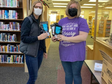 Two women wearing masks standing next to one another holding Deterra Medication Disposal Bags