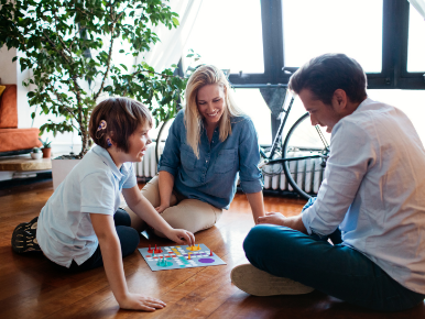 Family of three sitting on the floor around a board game