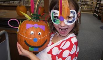 Child wearing mask holding a pumpkin decorated with a face