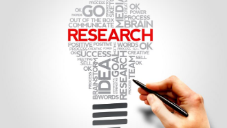 "Word cloud shaped like a light bulb with the word ""research"" large and in red"