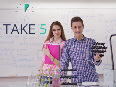 Two teens standing in front of a science board