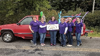 6 girls wearing jeans and purple shirts standing in a line in front of a truck holding a sign that says Kinsman Free Public Library